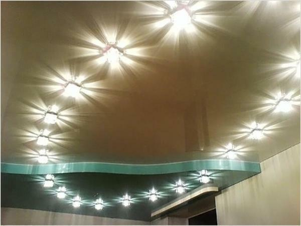 Recessed luminaires in the stretch ceiling are located in the space formed by the ceiling cap and the stretch ceiling