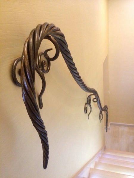 Forged handrails zmeyatsya the wall. It is evident that the blacksmith with fantasy.