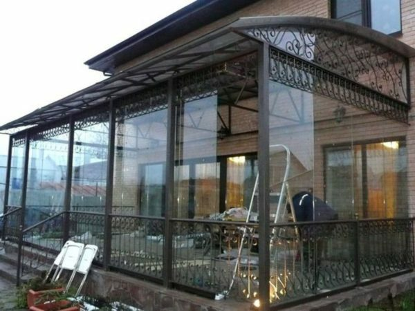 Fence and porch awning polycarbonate decorated with elements of forging.