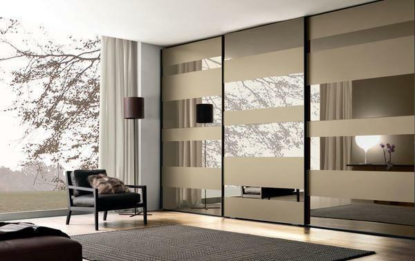 Stylishly complement the interior of the modern living room will help a beautiful wardrobe with mirrored doors