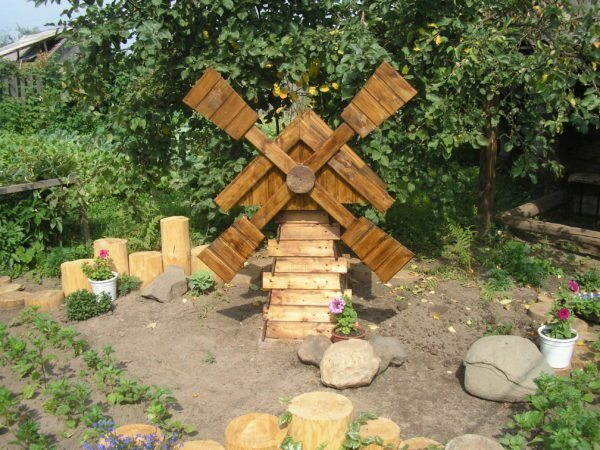 Decorative wooden mill can be a great decoration for your country site