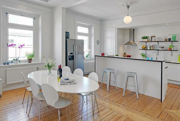 The kitchen-living room in the Scandinavian style is built-in furniture, wooden flooring, and an open plan space